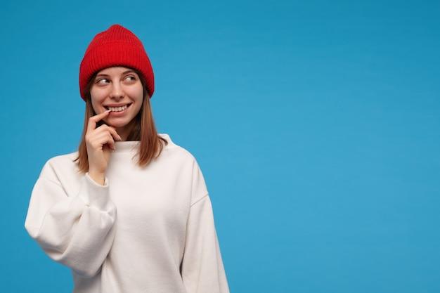 10代の少女、ブルネットの髪の幸せそうな女性。白いセーターと赤い帽子を着ています。彼女の口の隅に触れて微笑む。青い壁に隔離されたコピースペースで右を見る