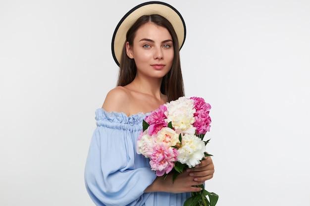 십 대 소녀, 갈색 머리 긴 머리를 가진 행복 한 찾고 여자. 모자와 파란 예쁜 드레스를 입고. 아름다운 꽃을 들고. 흰 벽 위에 절연보고
