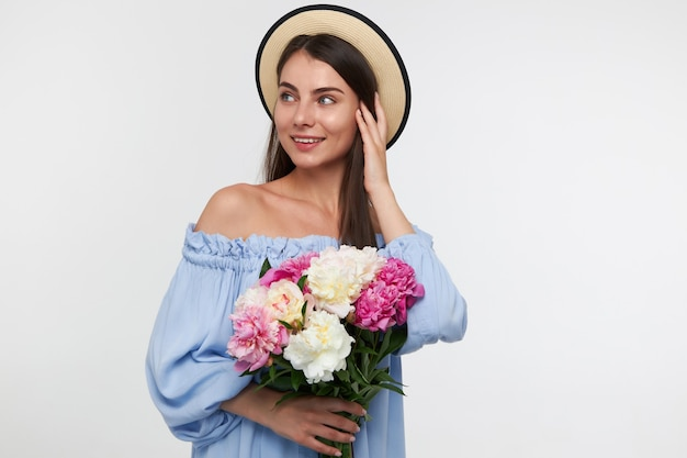 Teenage girl, happy looking woman with brunette long hair.wearing a hat and blue pretty dress. holding a bouquet of flowers and touching hair. watching to the left at copy space over white wall