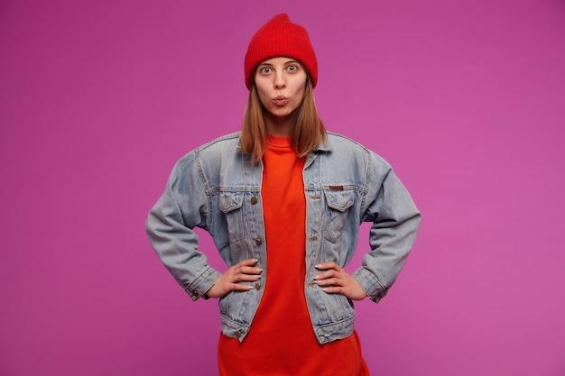 십 대 소녀, 갈색 머리 긴 머리를 가진 행복 한 찾고 여자. 청바지 재킷, 빨간 스웨터 및 모자를 착용하십시오. 허리에 손을 대고 보라색 벽에 키스하는 얼굴을 만들어