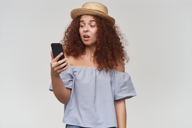 Teenage girl, happy looking woman with curly ginger hair. wearing striped off-shoulders blouse and hat. holding and watching at her smartphone, unhappy face. stand isolated over white wall
