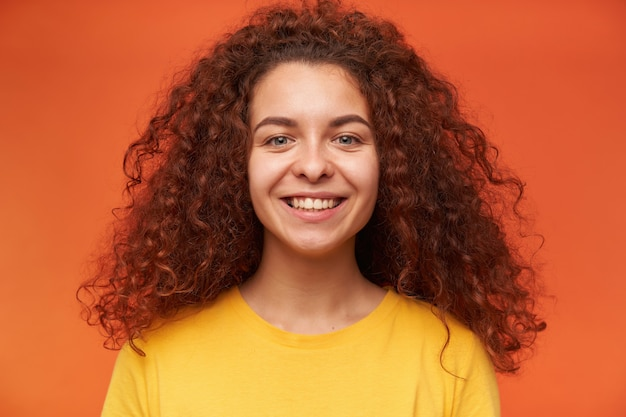 10代の少女、黄色のtシャツを着て生姜巻き毛の幸せそうな女性