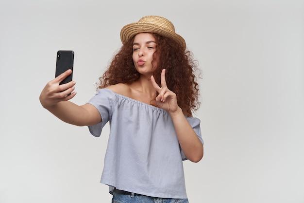 십 대 소녀, 생강 곱슬 머리를 가진 행복 한 여자. 스트라이프 오프 숄더 블라우스와 모자 착용. 스마트 폰으로 셀카를 찍고 평화 기호와 키스를 보여줍니다. 흰 벽 위에 절연 스탠드