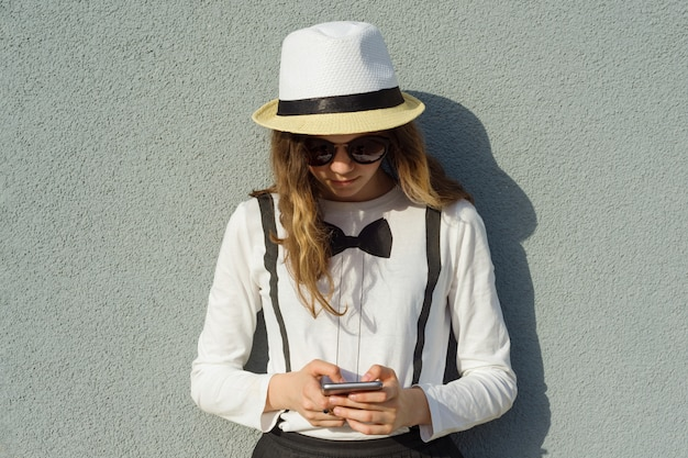Teenage girl in hat, girl uses smartphone
