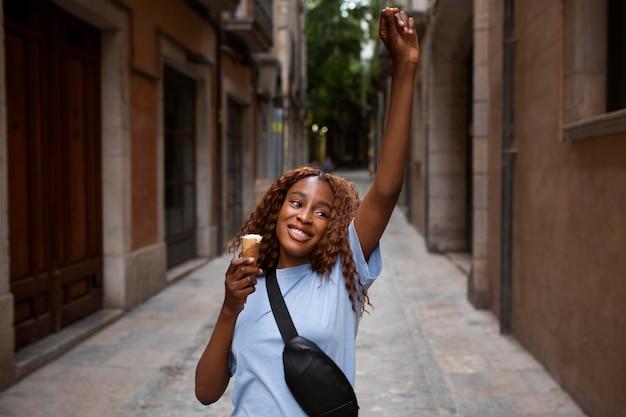 Девочка-подросток с мороженым на открытом воздухе и улыбается