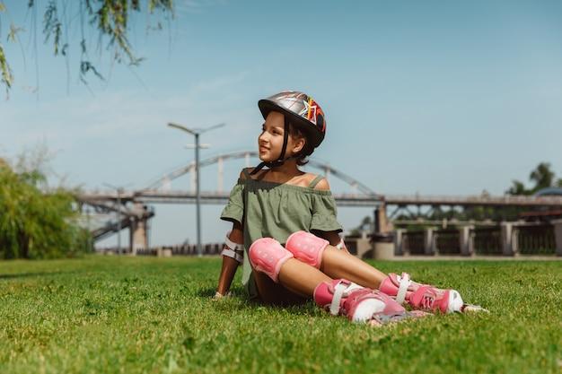 Ragazza adolescente in un casco impara a guidare sui pattini a rotelle tenendo un equilibrio o sui rollerblade e girare per la strada della città nella soleggiata giornata estiva