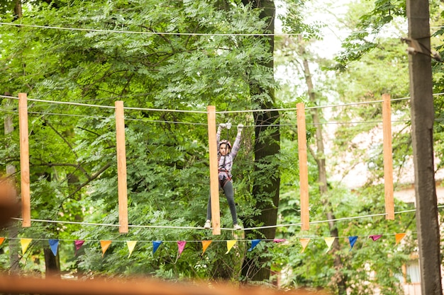 Teenage girl in a helmet and safety equipment in adventure ropes park on the background of nature