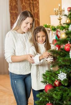 クリスマスツリーを飾る母親を助ける10代の少女
