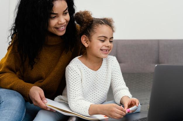 온라인 학교에 노트북을 사용하는 여동생을 돕는 십 대 소녀