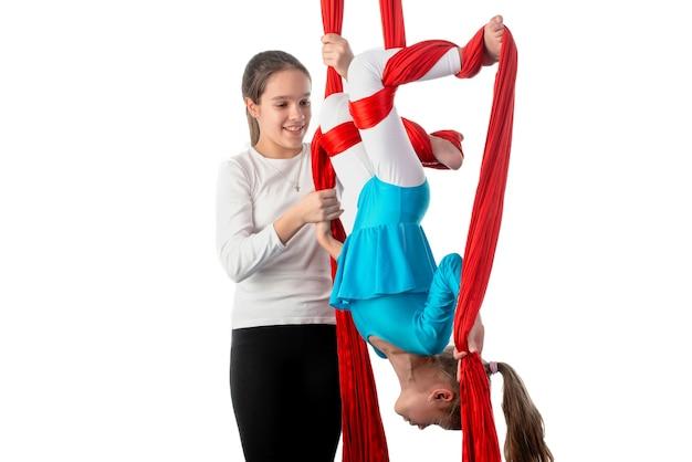 Девочка-подросток помогает сестренке как следует закрепиться на красных воздушных ленточках во время упражнений по акробатике