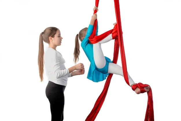 Девочка-подросток помогает сестренке как следует закрепиться на красных воздушных ленточках во время выполнения упражнений по акробатике