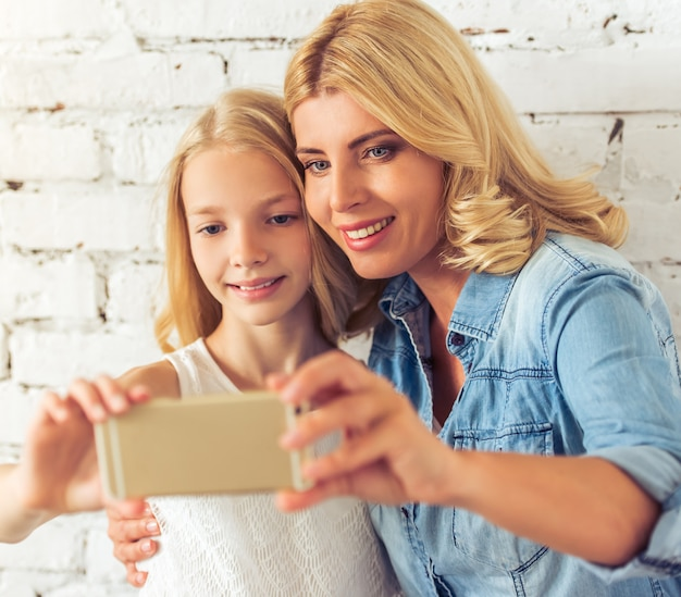 Teenage girl and her mother are making selfie.