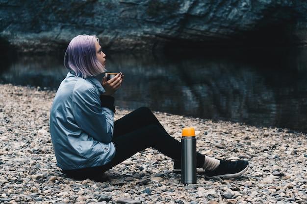 Путешественник девочка-подросток отдыхает с кружкой на берегу реки, глядя на прибрежные скалы