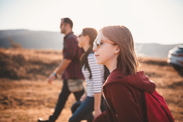 Teenage girl hiking on a mountain road with family