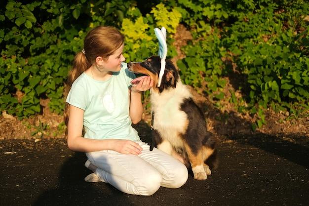 10대 소녀는 토끼 귀를 착용한 재미있는 귀여운 호주 셰퍼드 3색 강아지를 안고 있습니다. 행복한 부활절. 휴일. 집 밖의. 봄 공원에서.