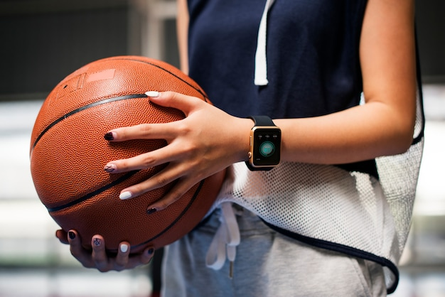 Teenage girl holding a basketball on the court