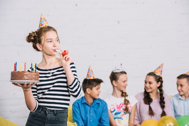 Teenage girl holding birthday cake in hand blowing party horn standing in front of her friends sitting together
