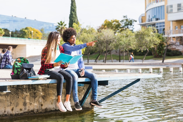 Teenage girl holding book in hand looking at his boyfriend showing something near the lake