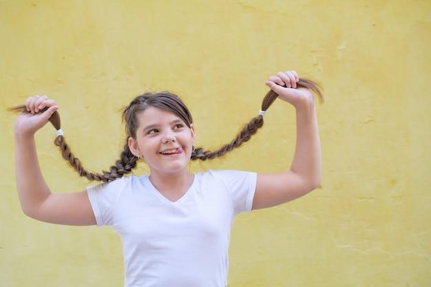 Девочка-подросток, держащая в руках косы, улыбается и показывает язык