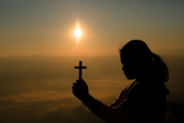 Teenage girl holding cross with praying. peace, hope, dreams concept.