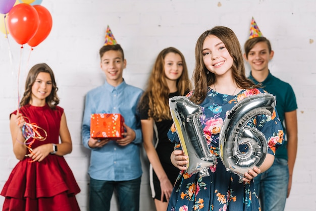 A teenage girl holding grey number 16 foil balloon number standing in front of friends