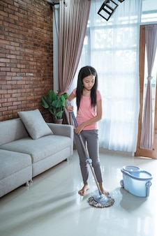 Teenage girl holding a mop stick doing household chores is mopping the living room