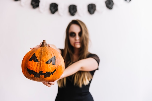 Teenage girl holding pumpkin