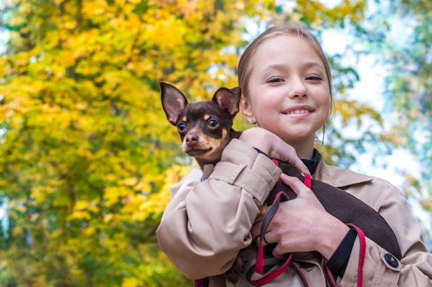 Teenage girl holding a toy terrier dog in her arms