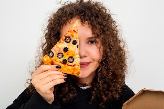 10代の少女はピザのスライスと笑顔を保持しています。