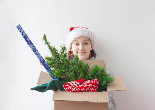 A teenage girl holds out a box with an artificial christmas tree, a christmas sweater and a roll of wrapping paper