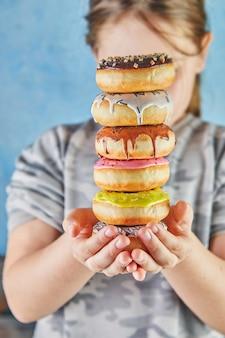 십 대 소녀는 두 손으로 다 색된 도넛의 스택을 보유하고있다.