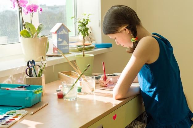 Teenage girl at home draws watercolor