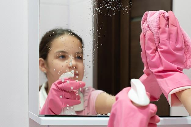 10代の少女は、スプレーボトルに洗浄剤を入れ、バスルームの鏡をぼろきれで洗う