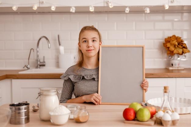 회색 드레스를 입은 십대 소녀가 전통적인 사과 파이를 요리 할 것입니다.