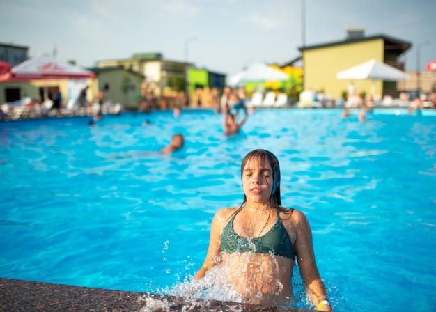 녹색 수영복에 10 대 소녀가 따뜻한 수영장에서 나온다