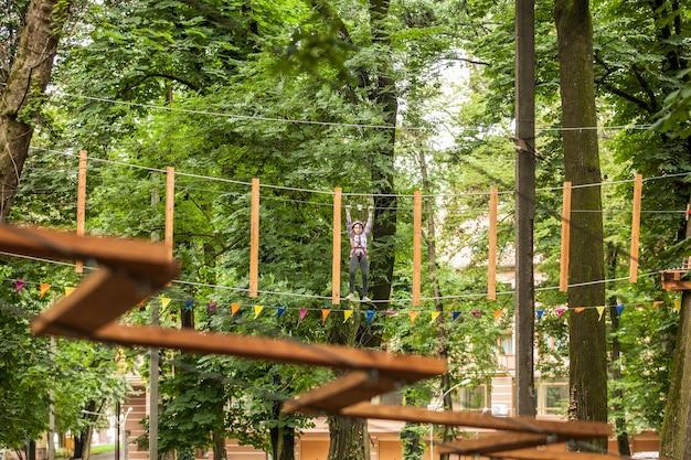 自然の背景にある冒険ロープ公園のヘルメットと安全装置の10代の少女