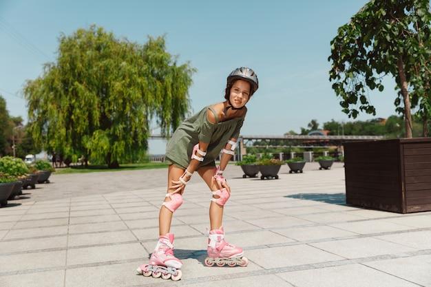 헬멧을 쓴 십대 소녀는 화창한 여름 날에 균형이나 롤러 블레이드를 들고 롤러 스케이트를 타고 도시의 거리에서 회전하는 법을 배웁니다. 건강한 라이프 스타일, 어린 시절, 취미, 여가 활동.