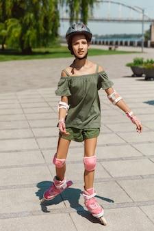 ヘルメットをかぶった10代の少女は、晴れた夏の日に、バランスまたはローラーブレードを持ってローラースケートに乗って街の通りでスピンすることを学びます