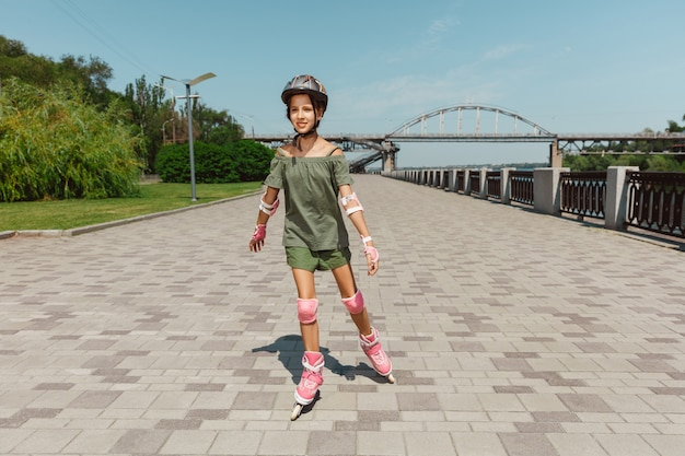 ヘルメットをかぶった10代の少女が屋外でローラースケートに乗ることを学ぶ