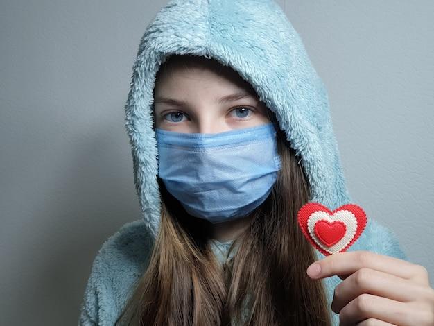 Девушка-подросток в медицинской маске держит в руке красное сердце, день святого валентина в карантине