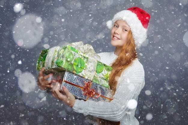 Девочка-подросток в шляпе санта-клауса держит подарочные коробки