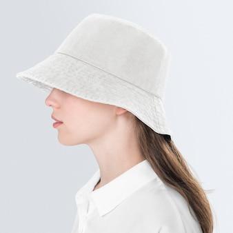 Девочка-подросток в бежевой шляпе-ведре для съемки уличной моды