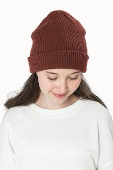 Девушка-подросток в цветной шапочке для фотосессии молодежной одежды