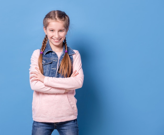 青い背景に自信を持ってポーズで10代の少女