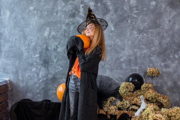 할로윈 휴가를 위한 장식 중 모자를 쓴 10대 소녀, 손에 거대한 호박. 유머 사진
