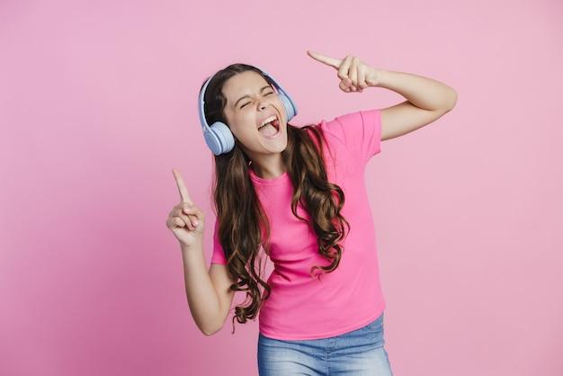 Девочка-подросток в наушниках слушает музыку, наслаждается любимой музыкой, танцует. милая девочка поет любимую песню