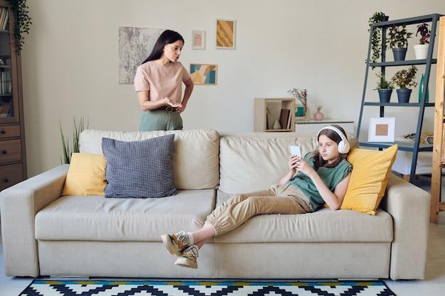 Девочка-подросток в наушниках использует смартфон и игнорирует мать, которая ругает ее за домашнее задание