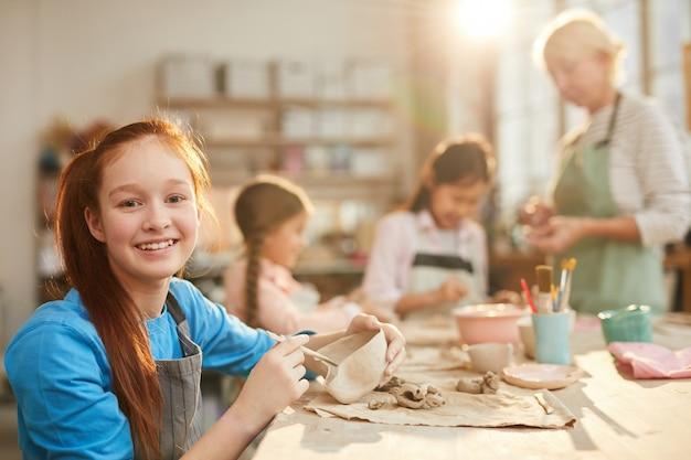Девочка-подросток в гончарной мастерской
