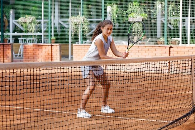 Девочка-подросток в спортивной одежде играет в теннис