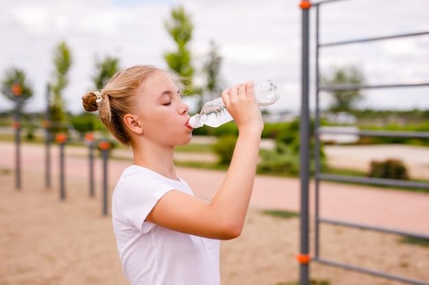 Девочка-подросток в военной форме работает на спортивной площадке и пьет чистую воду из прозрачной бутылки.